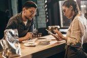 cílené žena pomocí tabletu s mladým kolegou poblíž tím v kavárně