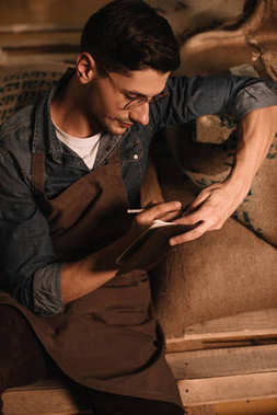 portrait of coffee roaster in eyeglasses and apron making notes in notebook
