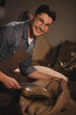 smiling worker in apron pouring coffee beans into sack bag