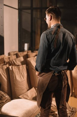 back view of coffee shop worker in apron looking at paper bags with coffee beans