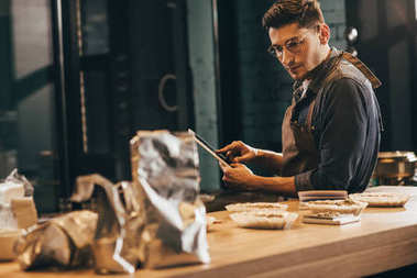 side view of focused worker in apron with tablet in coffee shop