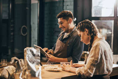 smiling man using tablet with young colleague near by at coffee shop