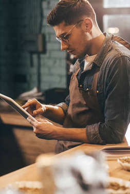 side view of focused worker in apron using tablet in coffee shop
