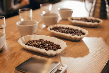close up view of arranged bowls with coffee beans and grind coffee for food function on wooden tabletop