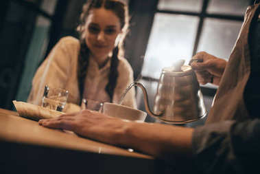 selective focus of man pouring hot water into bowl with grind coffee