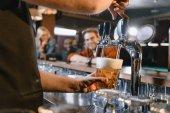 immagine potata di barman birra di versamento in vetro al bar