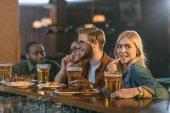 Fotografie atraktivní multikulturní přátelé, jídlo a pití na baru
