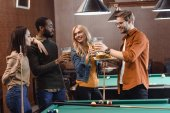 Photo company of multiethnic friends eating and drinking beside pool table at bar