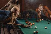 Fotografia giovani amici multietnici attraenti che giocano in piscina al bar