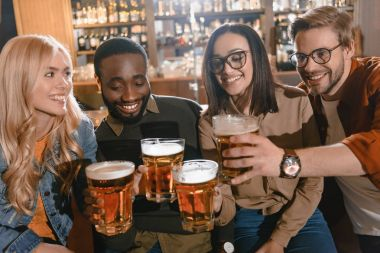 cheerful multiculture friends drinking beer together at bar