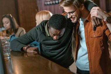 very drunk african american man at bar with friends
