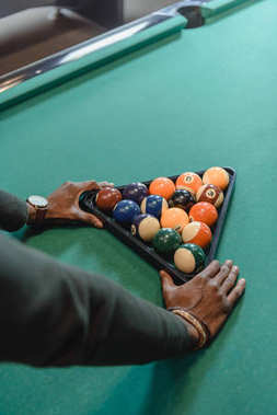 cropped image of male hands forming set of billiard balls by triangle