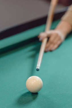 cropped image of hand with cue over pool table