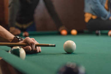 cropped image of friends playing in pool at bar