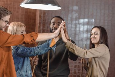 company of friends holding cues and giving high five to each other at bar