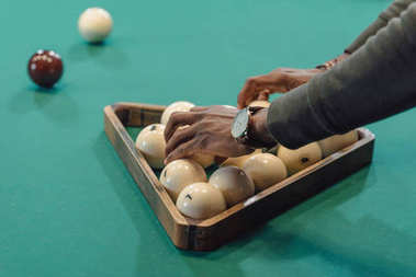 cropped image of male hands forming balls set by triangle on pool gambling table