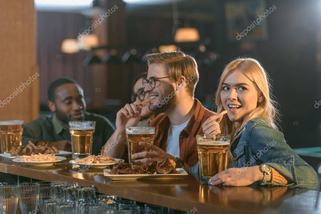 attractive multiculture friends eating and drinking at bar