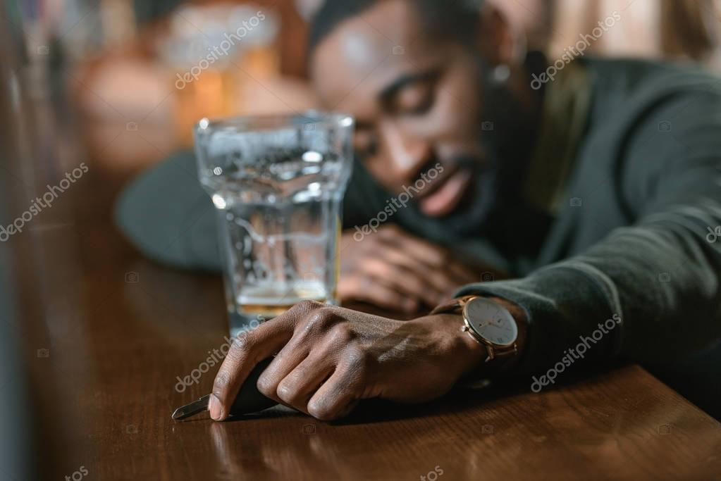 very drunk african american man with automobile keys at bar