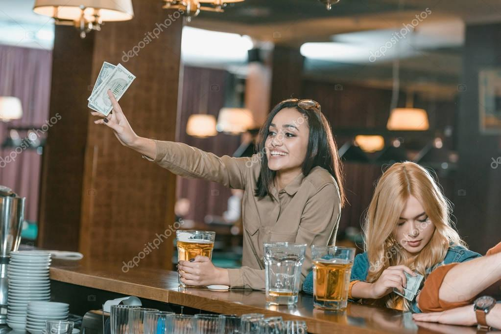 beautiful girl with money paying for drink at bar