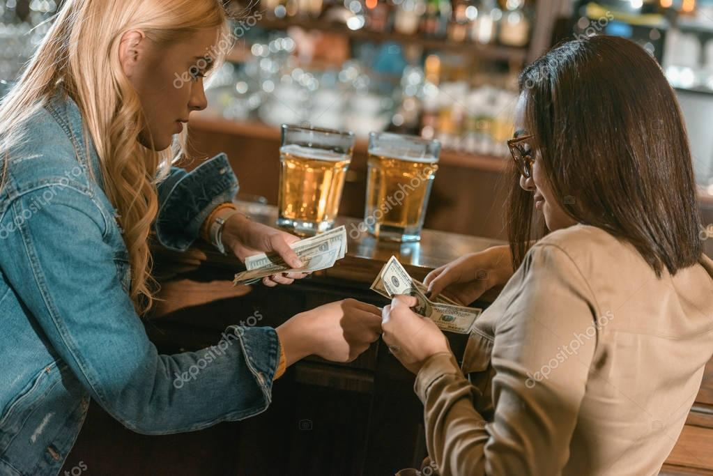 two girls with money paying for drink at bar