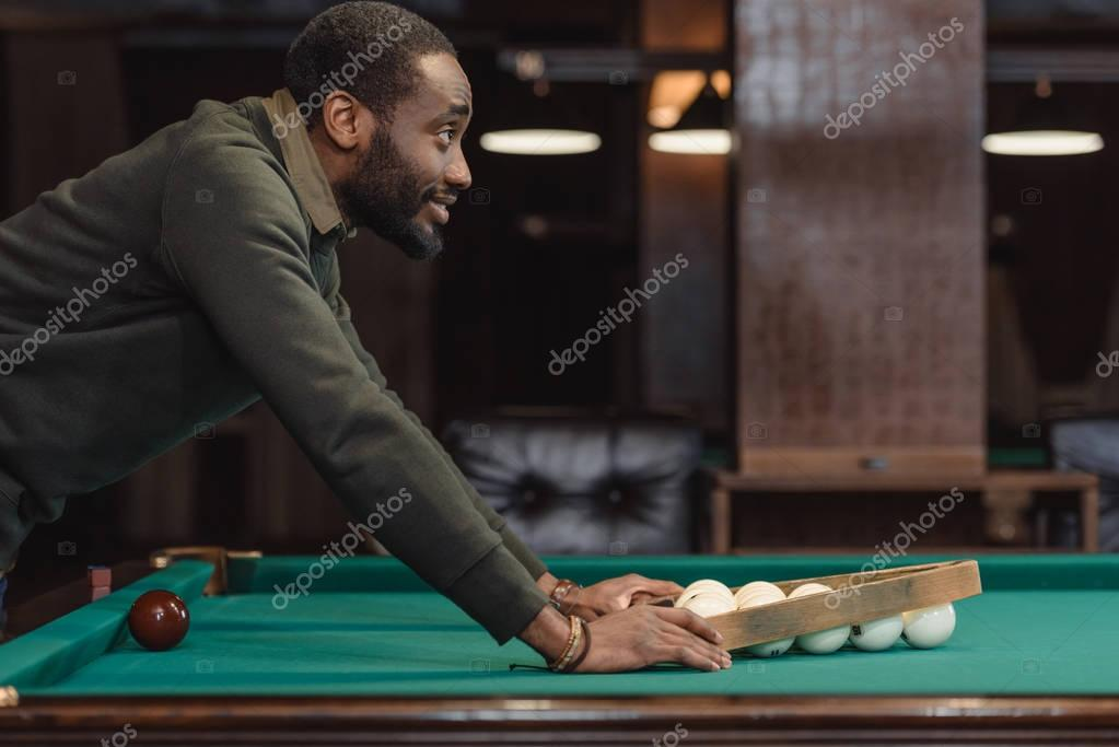 young man forming balls set by triangle on pool gambling table
