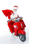 Santa Claus with big red bag sitting on red scooter, isolated on white