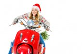 Fotografie beautiful woman in santa hat riding red scooter with christmas tree, isolated on white