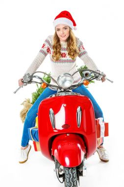 attractive woman in santa hat sitting on red scooter with gifts and christmas tree, isolated on white