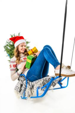 cheerful woman in santa hat sitting on sled with gift boxes and christmas tree, isolated on white