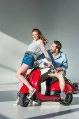 Fotografia giovani coppie allegre in posa vicino al motorino rosso insieme