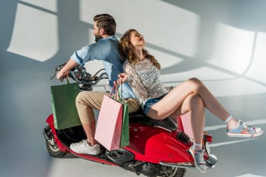 stylish couple in love with shopping bags sitting on red scooter