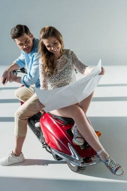 young couple looking for destination on map in hands while sitting on red scooter