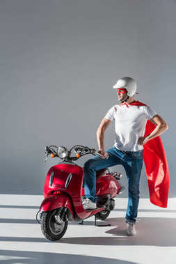 man in protective helmet and superhero costume standing at red scooter