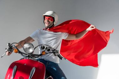 Happy man in protective helmet and superhero costume riding red scooter stock vector