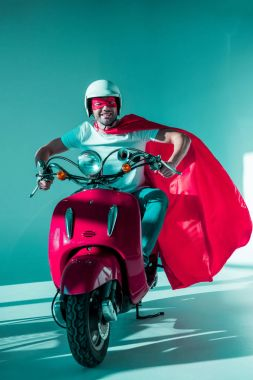 smiling man in protective helmet, superhero mask and cape riding red scooter