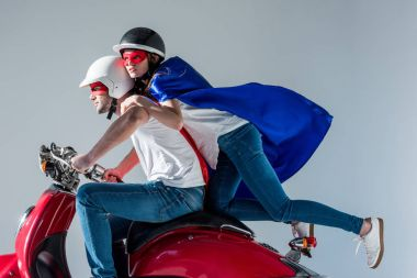 side view of couple in superhero costumes riding red scooter together