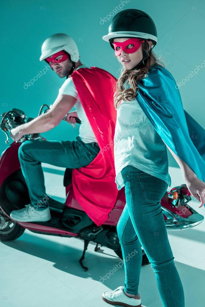 stylish couple in helmets and superhero costumes with red scooter looking at camera