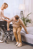 Photo wife helping husband with disability sit on wheelchair