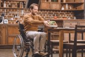 happy disabled man in wheelchair holding glass bowl of vegetable salad at home