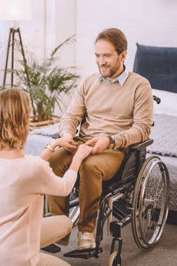 happy husband on wheelchair and wife holding hands