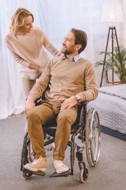 happy husband on wheelchair and wife looking at each other