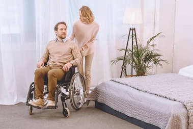 husband on wheelchair and wife in light bedroom