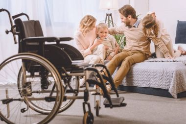happy father with disability and mother sitting with children on bed
