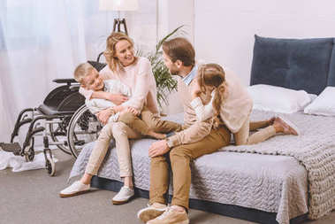 father with disability and happy mother sitting with children on bed