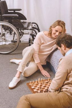 husband with disability and happy wife playing chess in bedroom