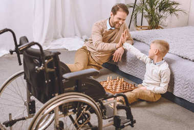 father with disability and son playing chess and giving high five