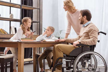smiling father on wheelchair and mother teaching children at home