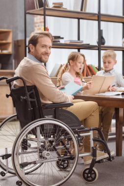 father on wheelchair teaching children at home and looking at camera