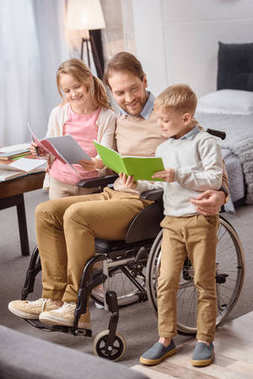 happy father on wheelchair teaching children at home