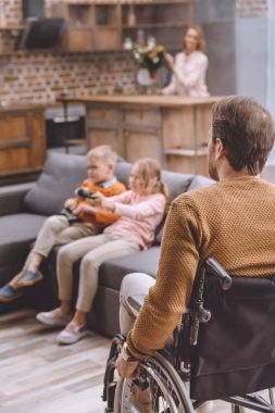 father on wheelchair looking how children playing video game